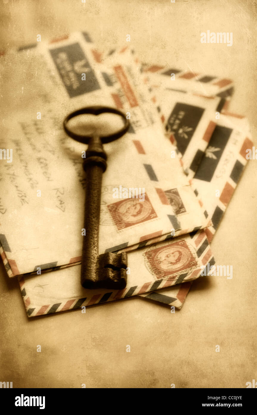 Rusted key over a collection of old letters - Stock Image