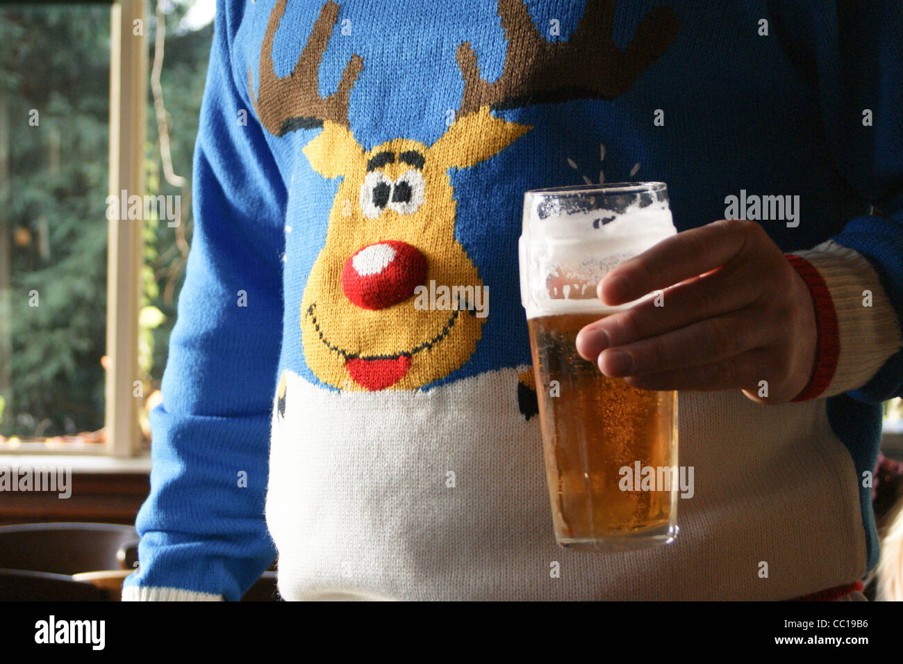 a-man-with-a-pint-of-fosters-lager-beer-in-a-christmas-jumper-with-CC19B6.jpg