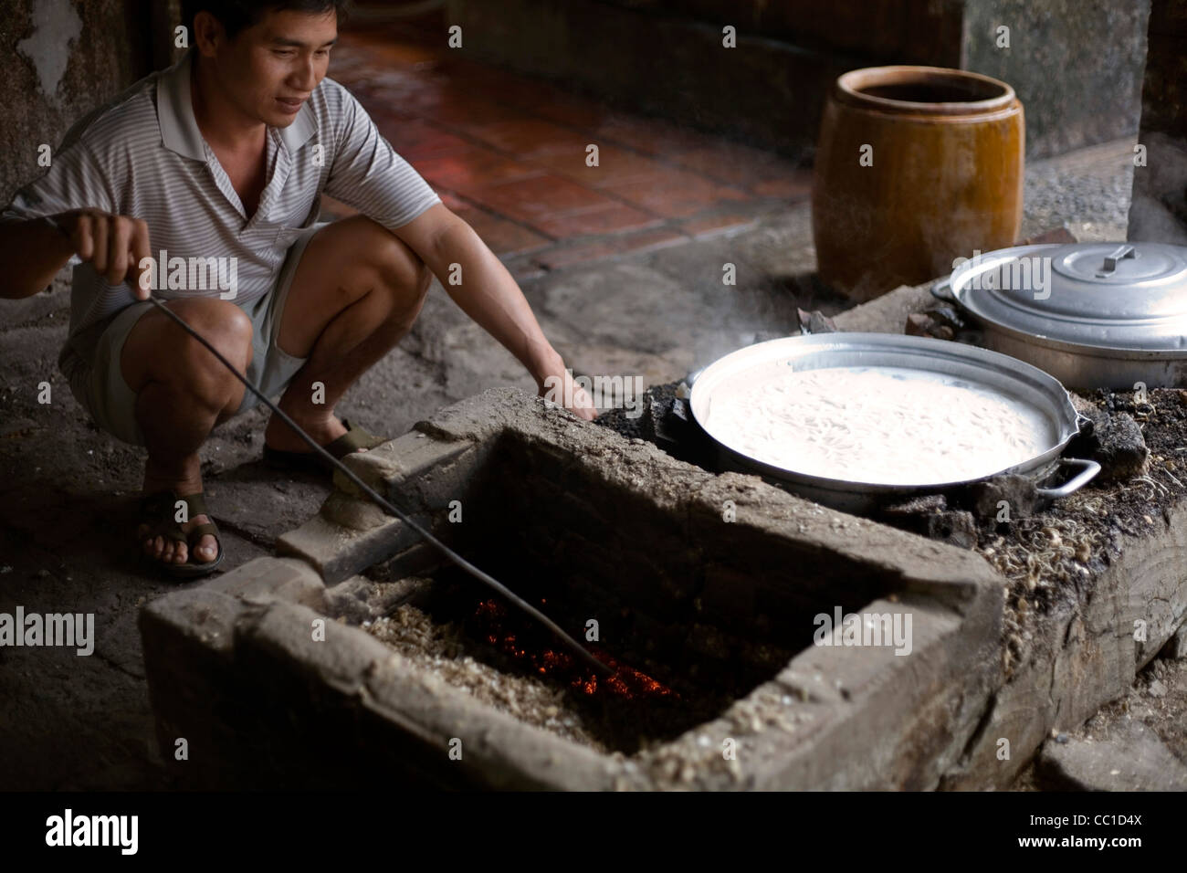 A man feed a fire to boil noodles in the traditional manner in a pot at a family farm, Tay Ninh, Vietnam - Stock Image