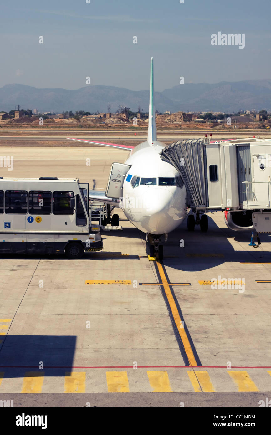 Passenger airplane being serviced at the gate Stock Photo
