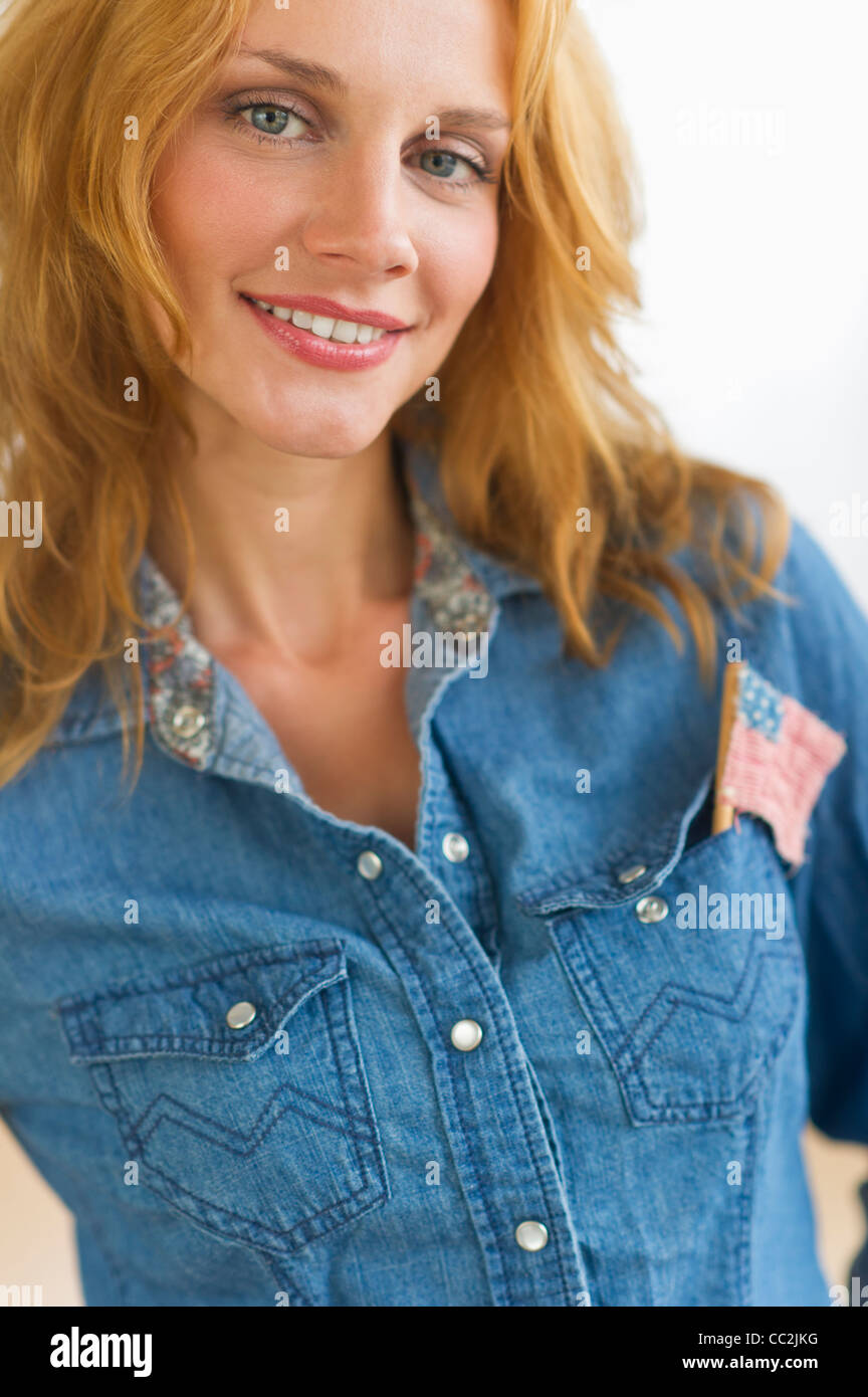 Studio portrait of young woman wearing denim jacket with US flag in pocket - Stock Image