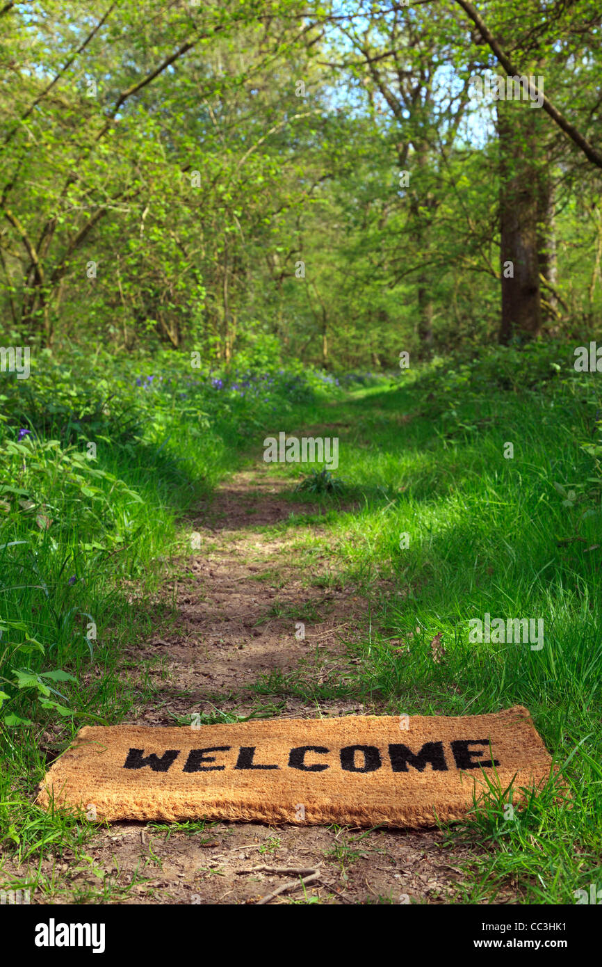 Concept photo of a Welcome doormat on a woodland footpath during springtime in vertical format. - Stock Image