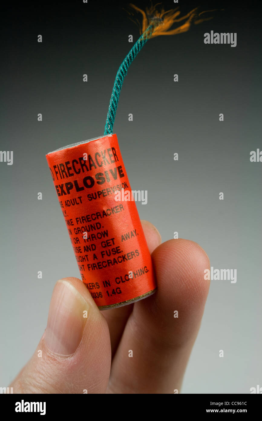 Large Firecracker in Hand - Burning Fuse - Stock Image