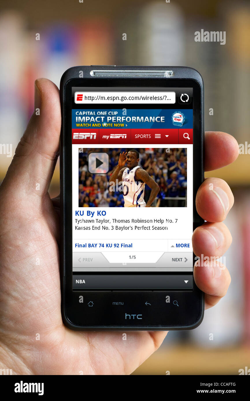Looking at the ESPN sports website on an HTC smartphone - Stock Image