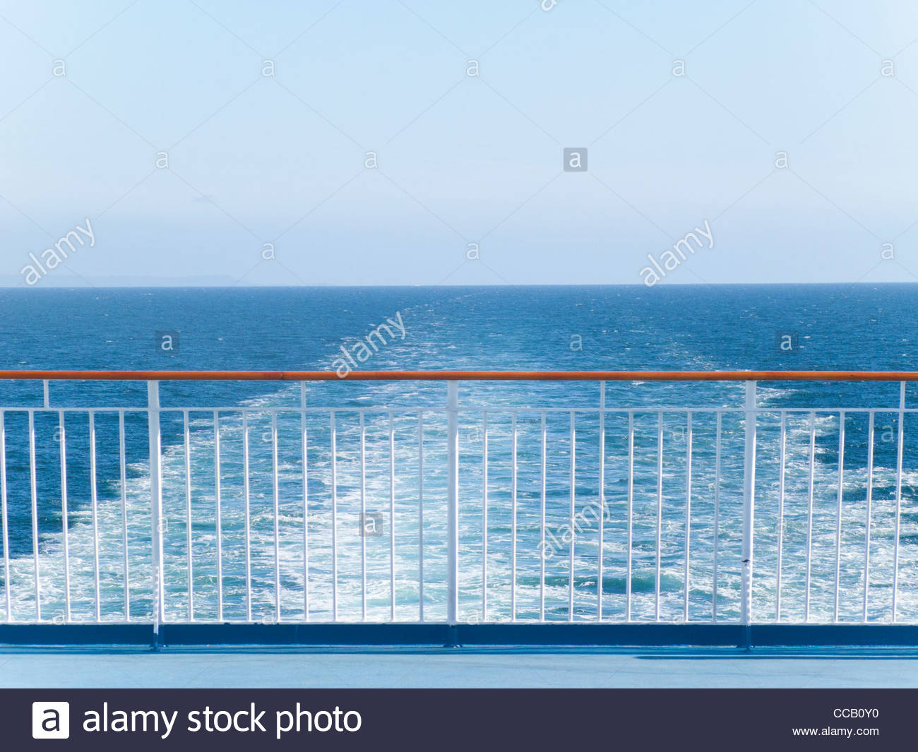 Railing of ship with ocean water in background - Stock Image