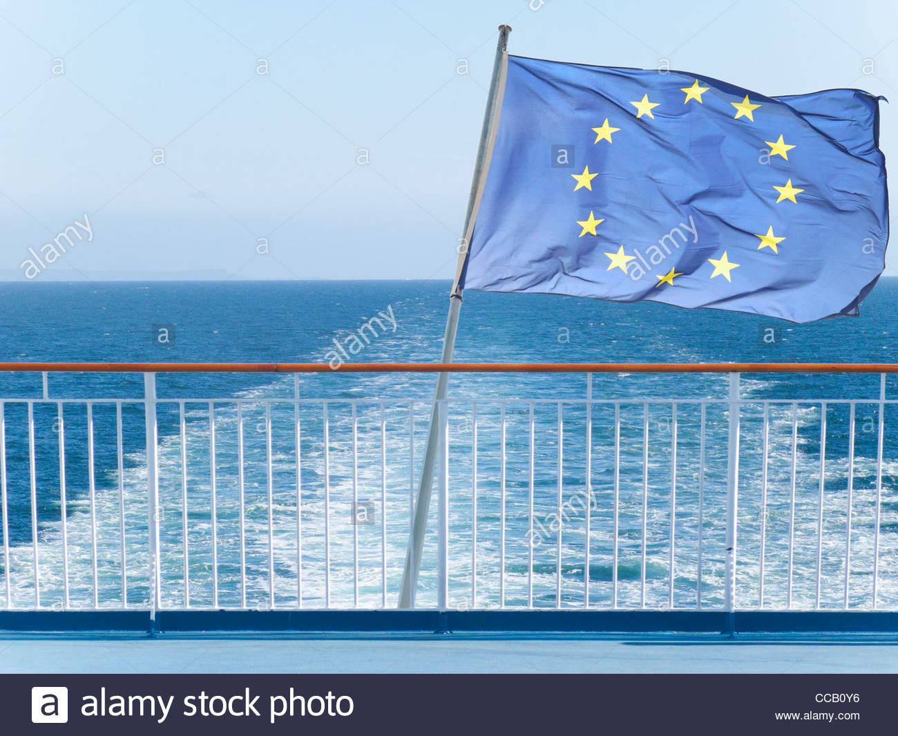 European Union flag on railing of ship with ocean water in background - Stock Image