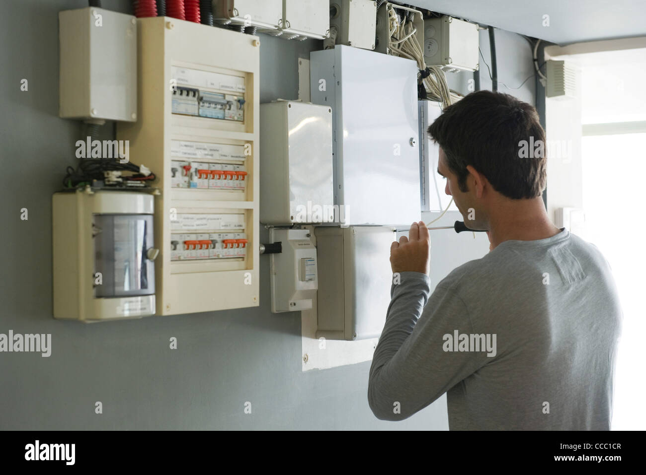 Man opening fuse box, rear view - Stock Image