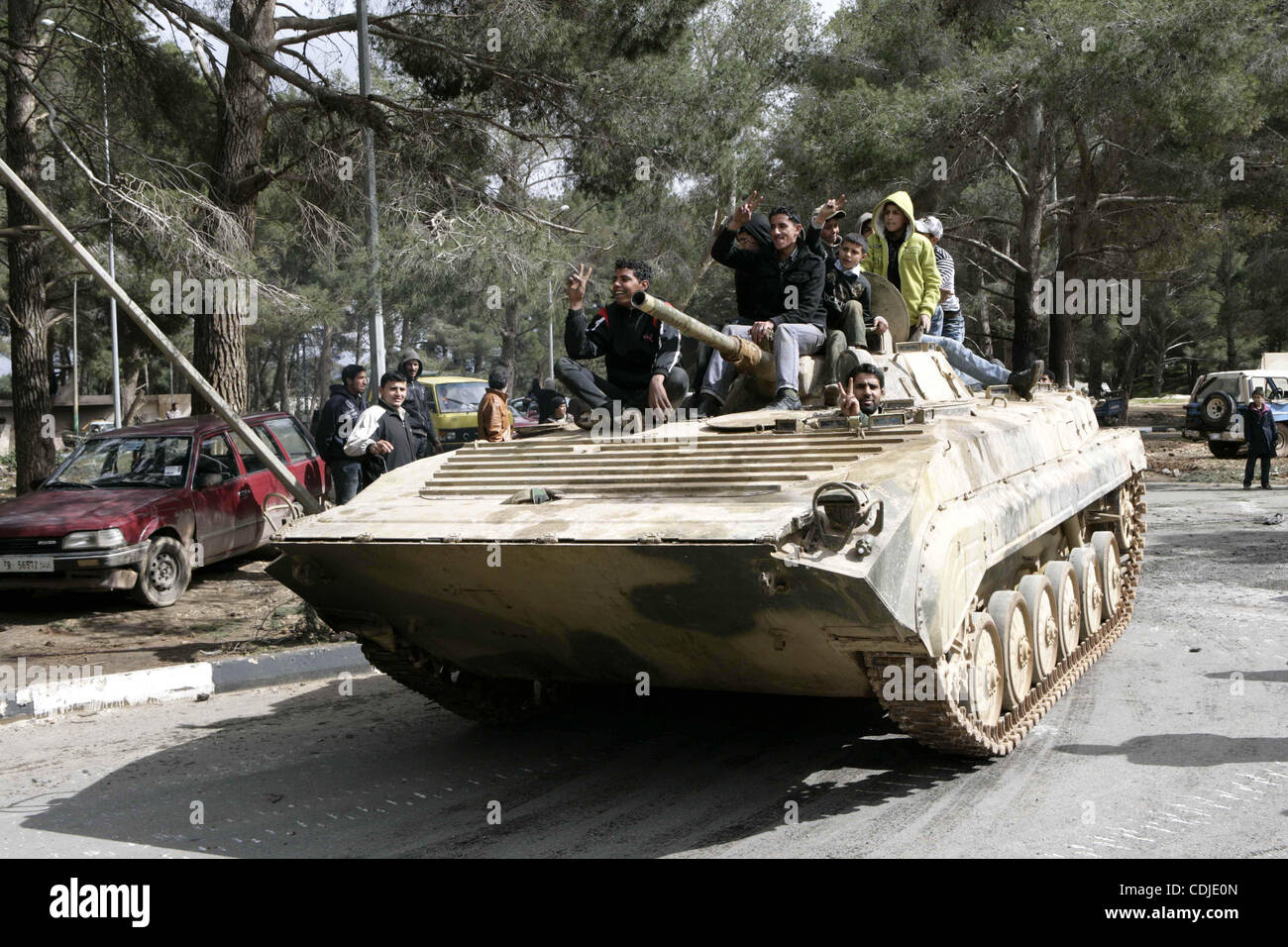 Anti-government protesters make victory signs as they stand on an army tank near a square where people are protesting - Stock Image