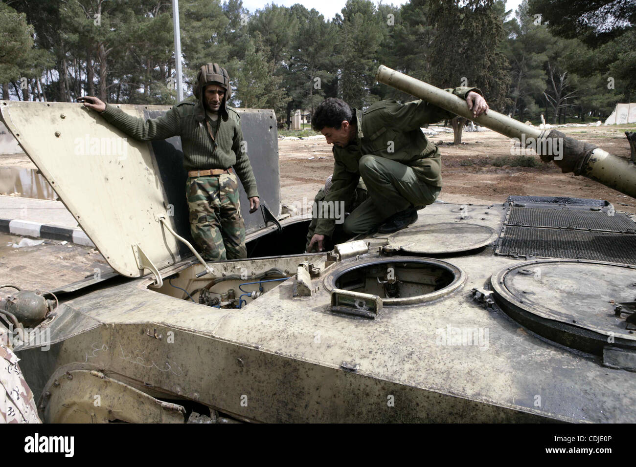 Anti-government protesters stand on an army tank near a square where people are protesting in ALbedi city, Libya, - Stock Image