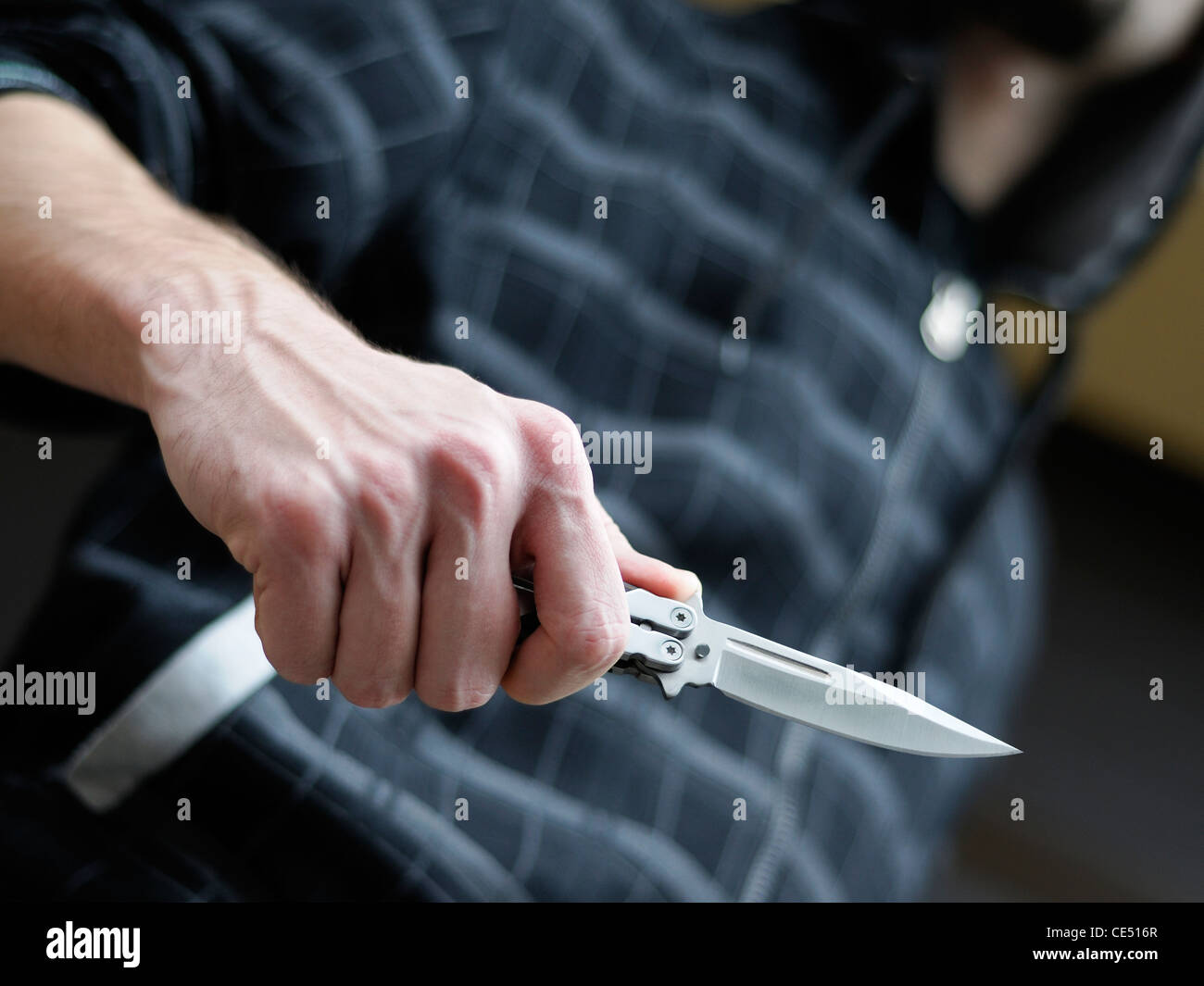 Knife Crime. Hooded Male Brandishing a Butterfly Knife. - Stock Image