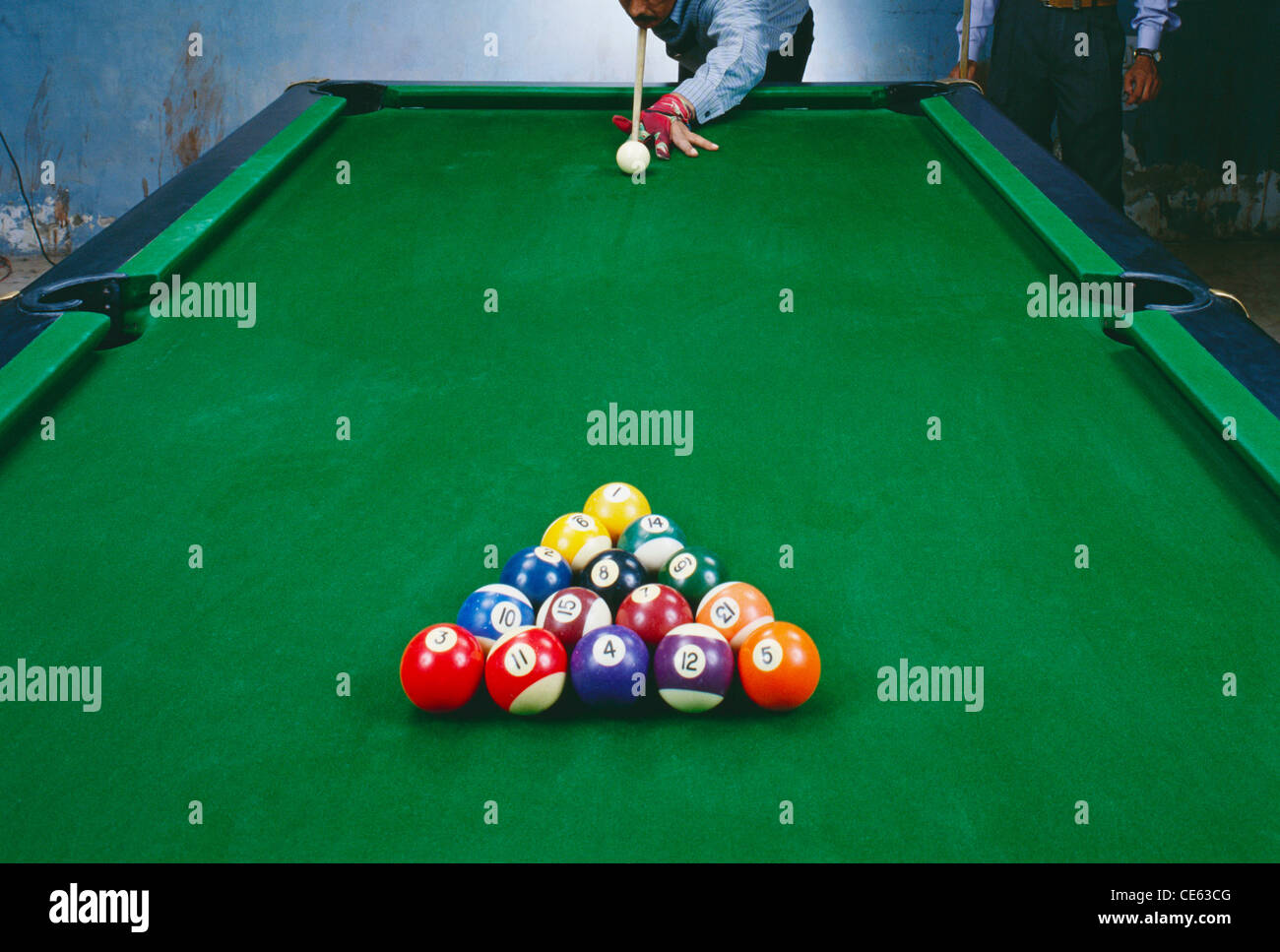 Rack of pool balls set up on table and man playing with cue ball ...