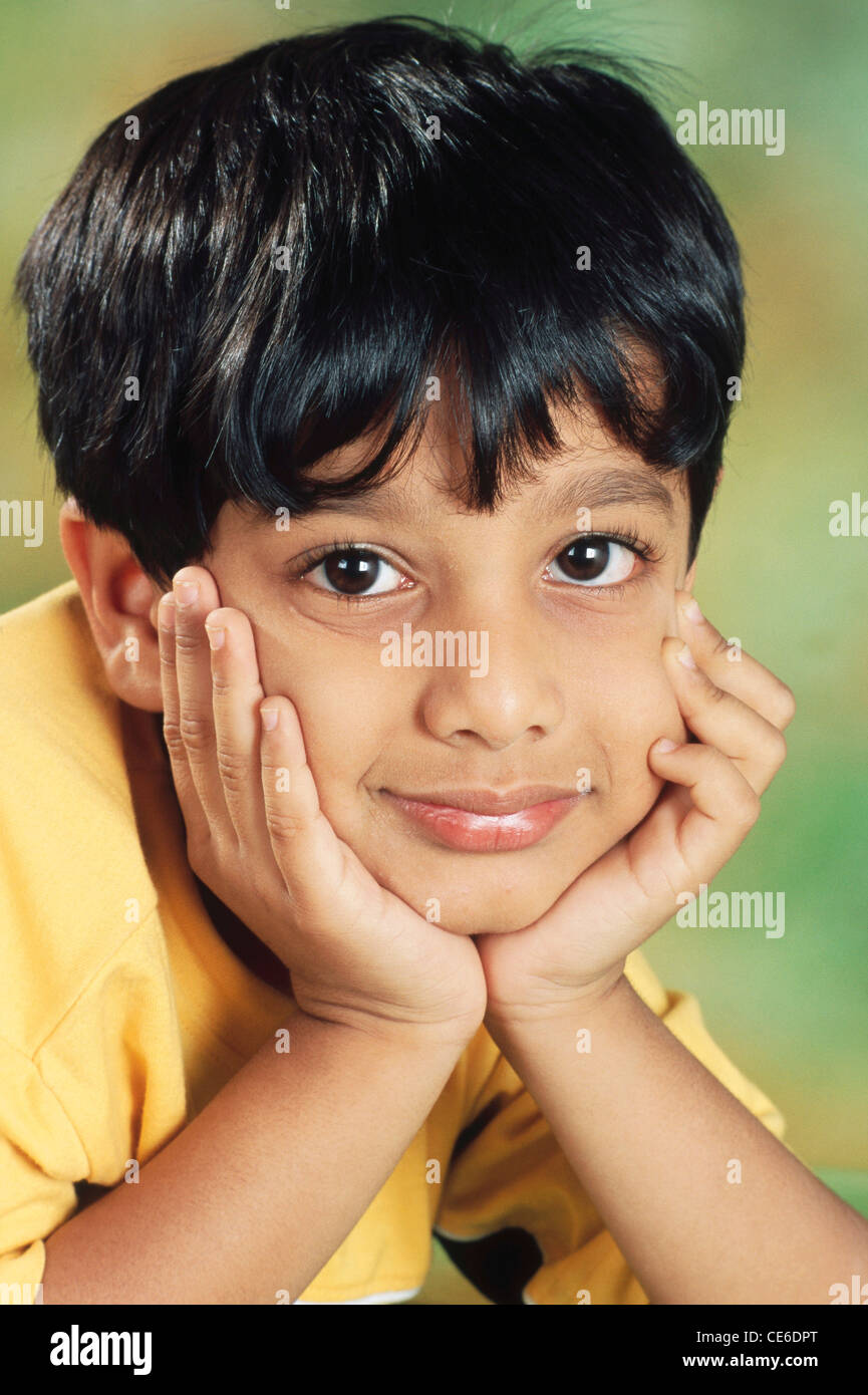 small young Indian boy face between both hands India   MR#152 Stock Photo
