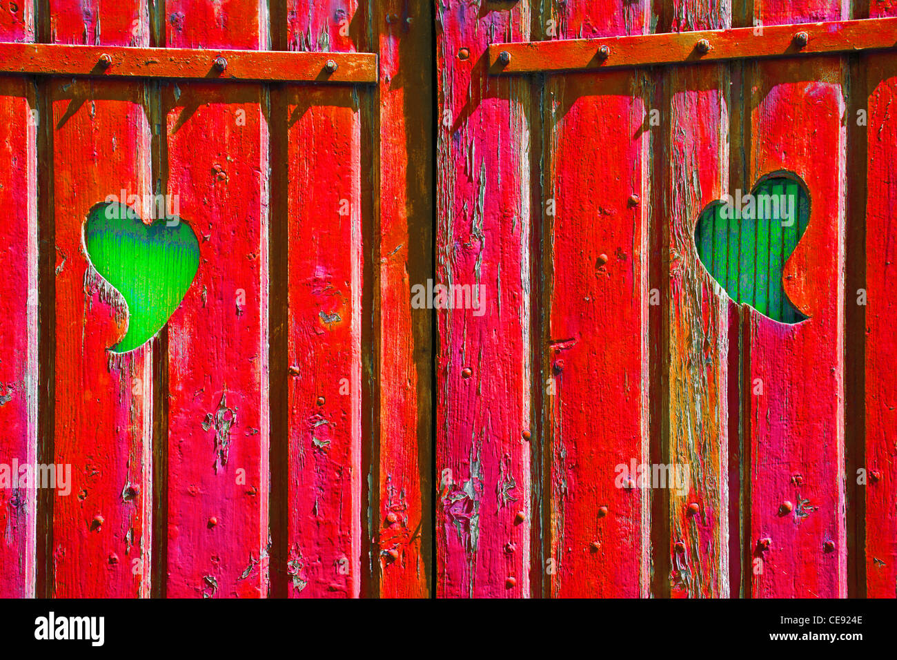 Two heart shapes cut into a red wooden gate revealing green wood behind, symbolic of envy, jealousy, passion - Stock Image