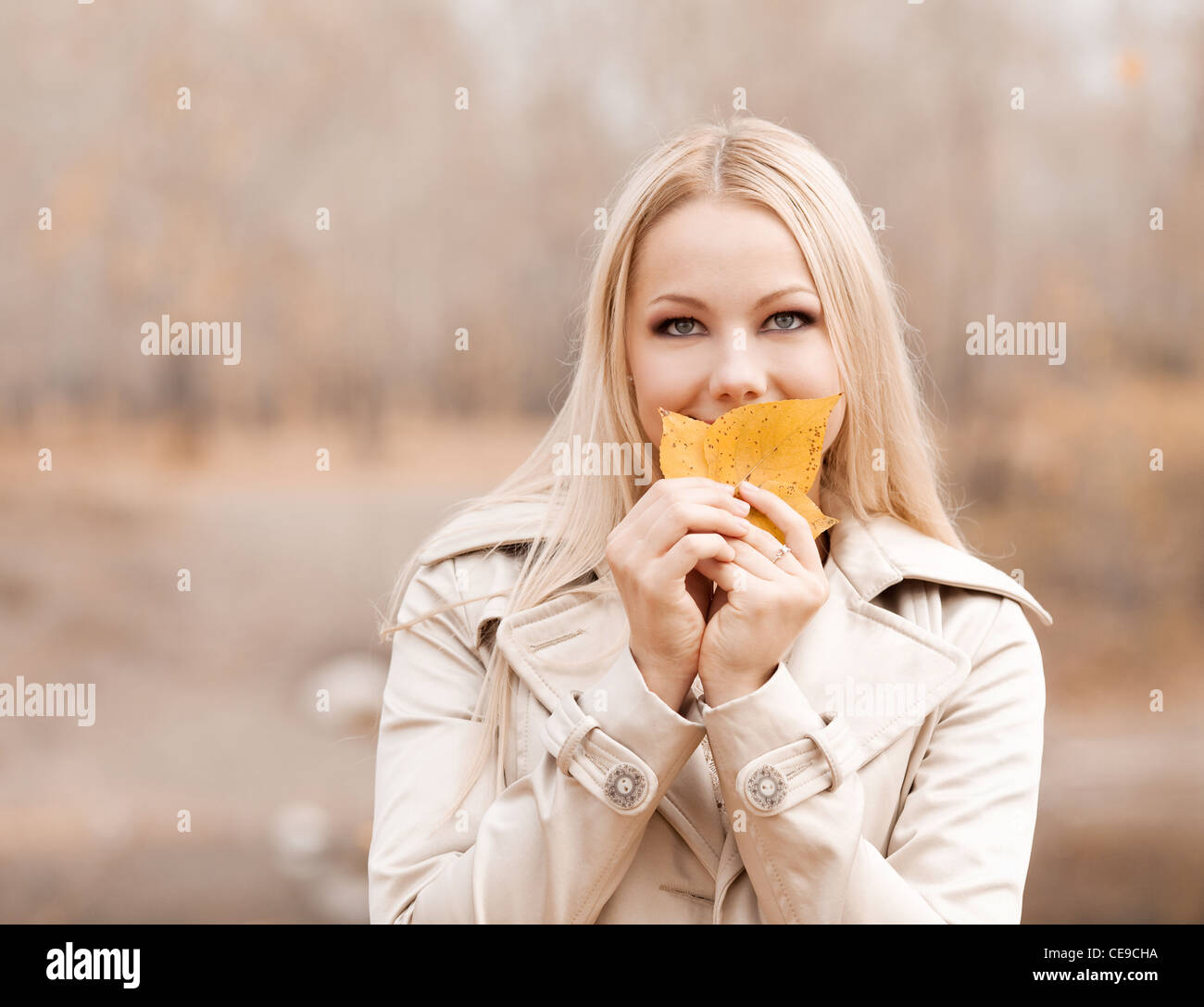 beautiful young blond woman spending time in the autumn park - Stock Image