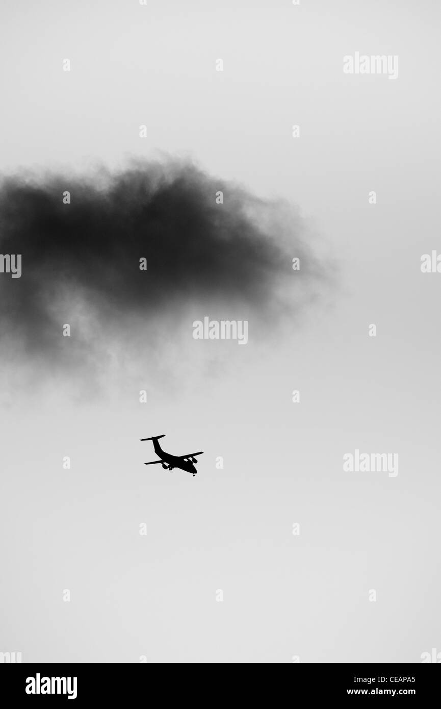 Airplane and dark cloud - Stock Image