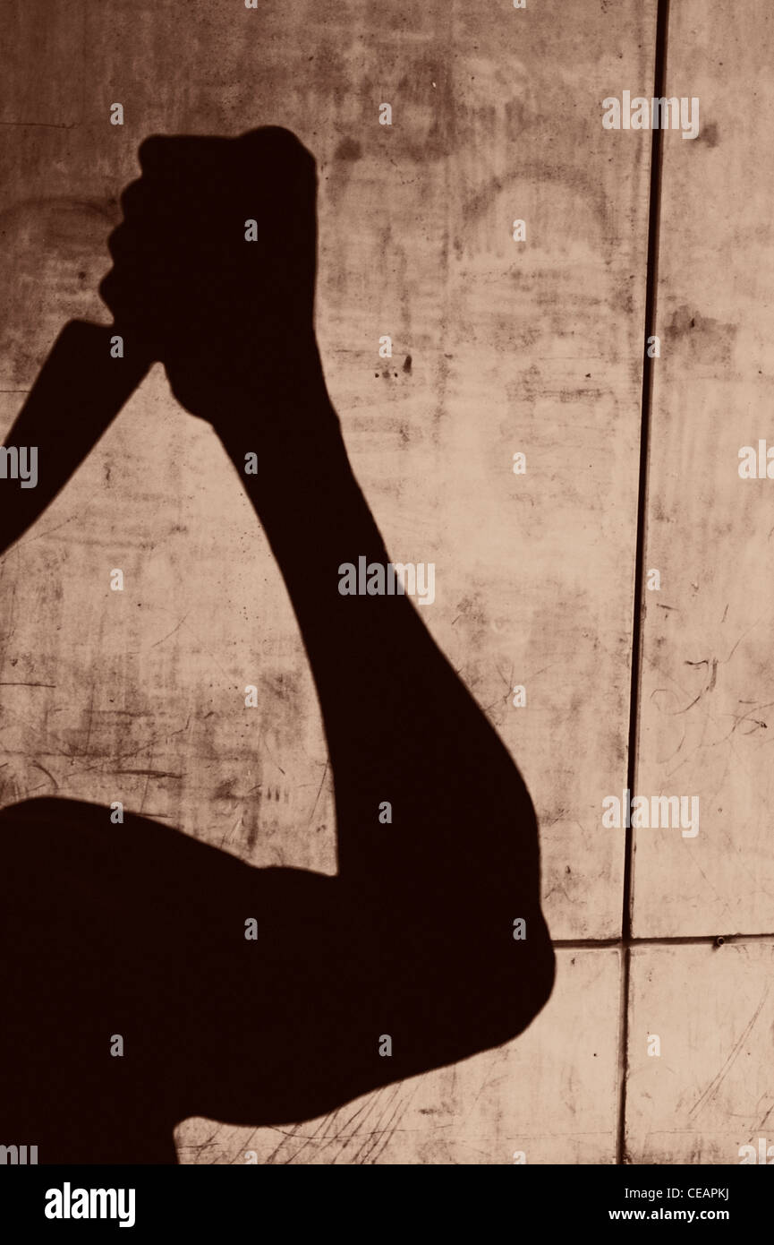 Silhouette of man with a knife in an urban setting - Stock Image