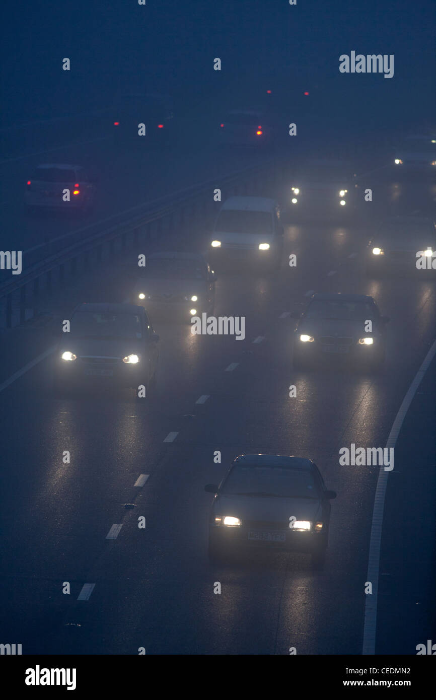Cars in the fog on road in England at night - Stock Image