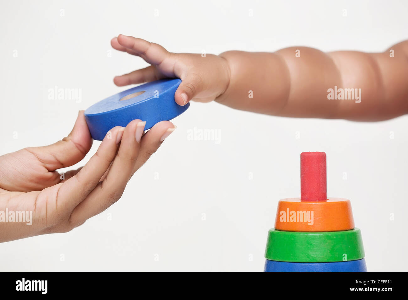 Adult hand gives a building block and baby learns to grip it - Stock Image