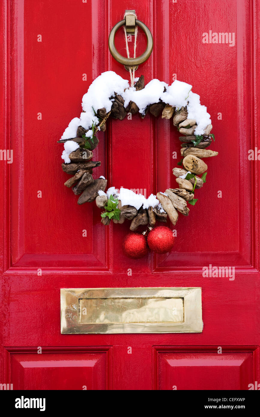 Decorative Driftwood Christmas Wreath Hanging On A Red Front Door