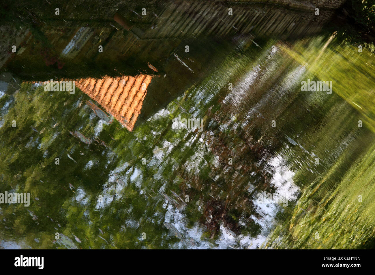 Reflections of green trees in a shallow rill of water. Water feature in a garden. Abstract view of water. Stock Photo