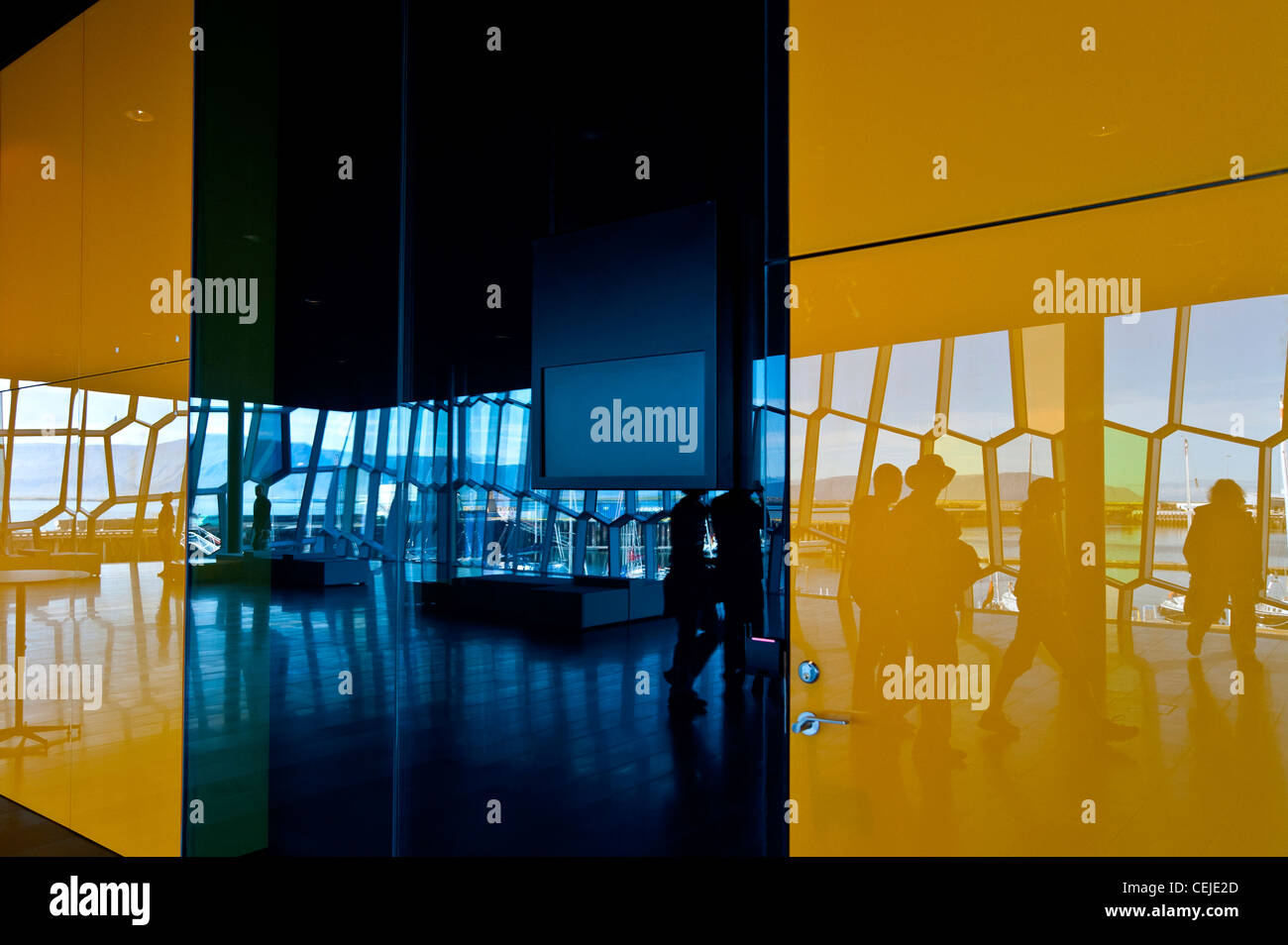 Reflection of group of people in colorful wall touring Harpa 'The Harp' concert hall in Reykjavik, Iceland. - Stock Image