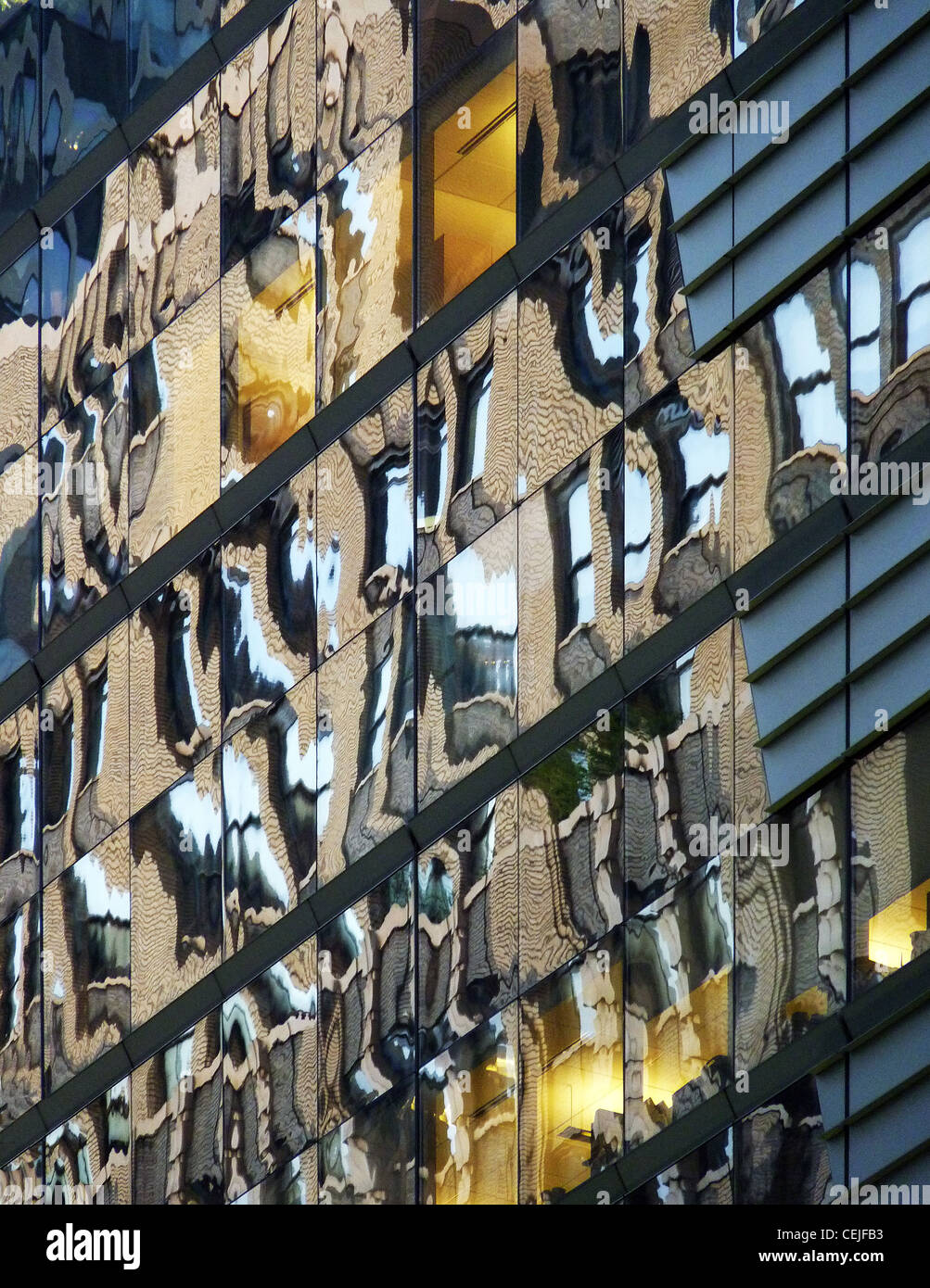 colors of surrounding buildings reflecting in a modern glass facade in 42nd street Manhattan - Stock Image