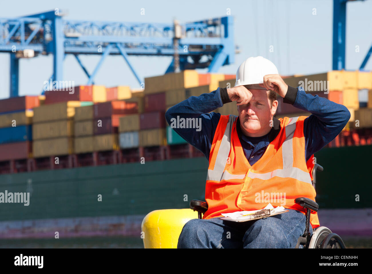 Transportation engineer in a wheelchair recording data for shipping containers and experiencing hot sun - Stock Image