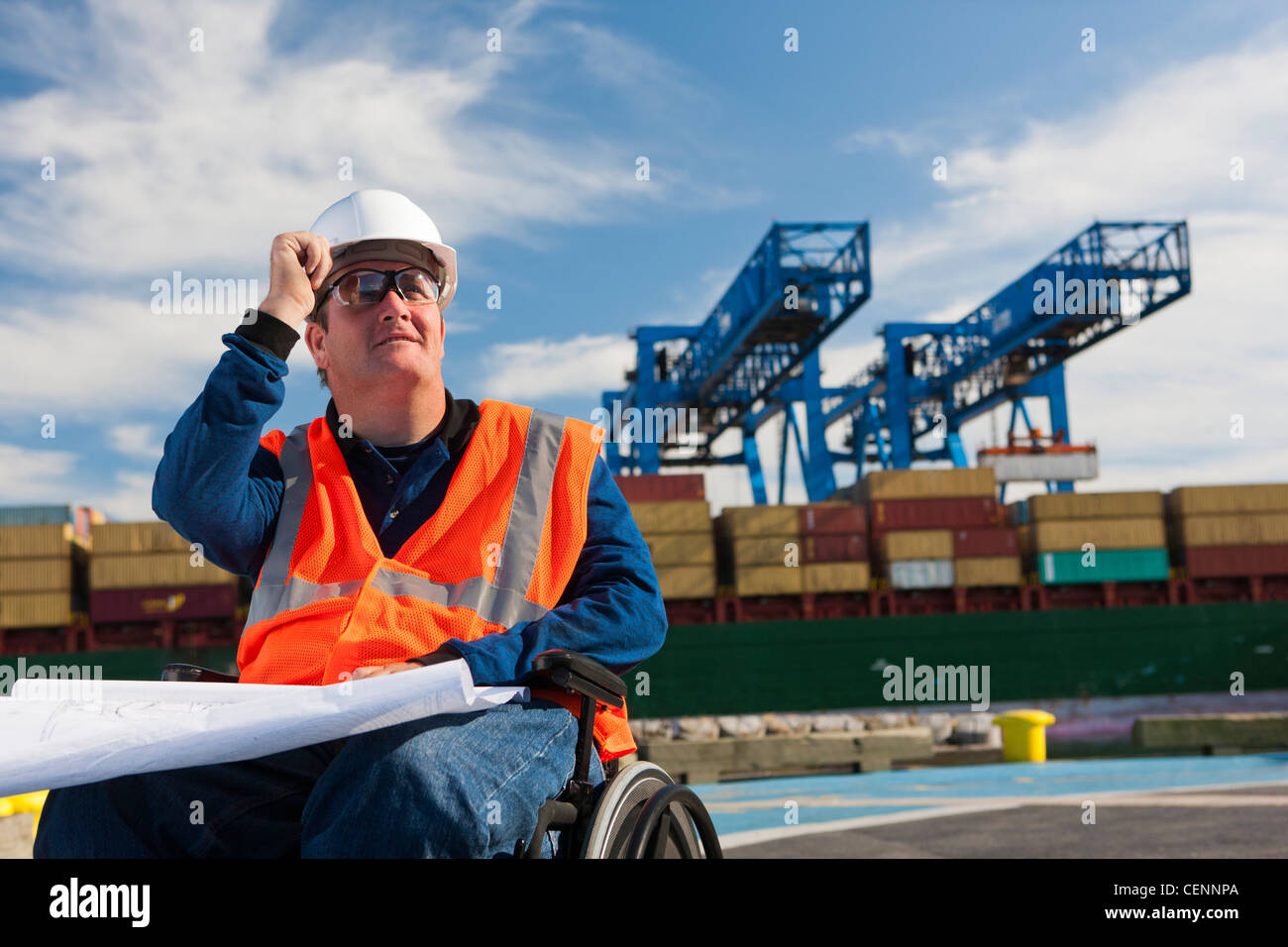 Transportation engineer in a wheelchair studying plans at shipping port - Stock Image