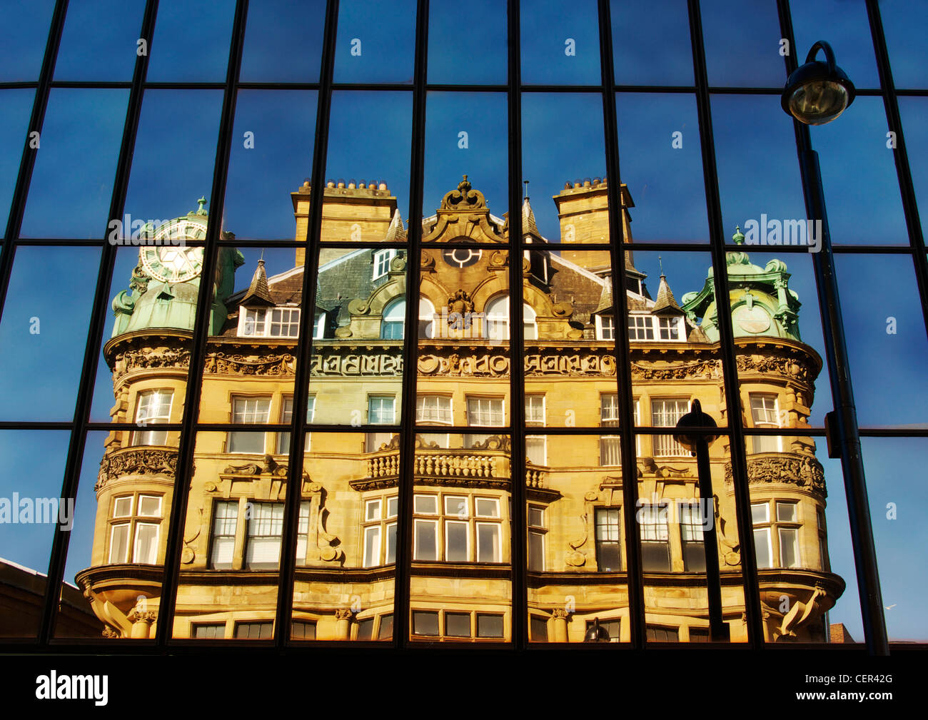 Historic building on Blackett Street reflected in glass panels. - Stock Image