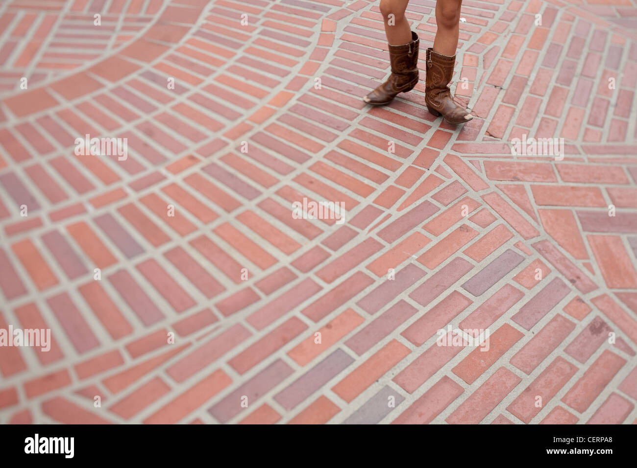 child legs in cowboy boots walking on brick design - Stock Image
