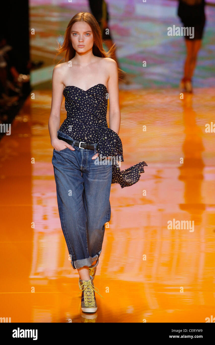 db44a21f847 DKNY Ready to Wear Spring Summer Model wearing a blue denim baggy jeans a  strapless fitted navy patterned bodice top