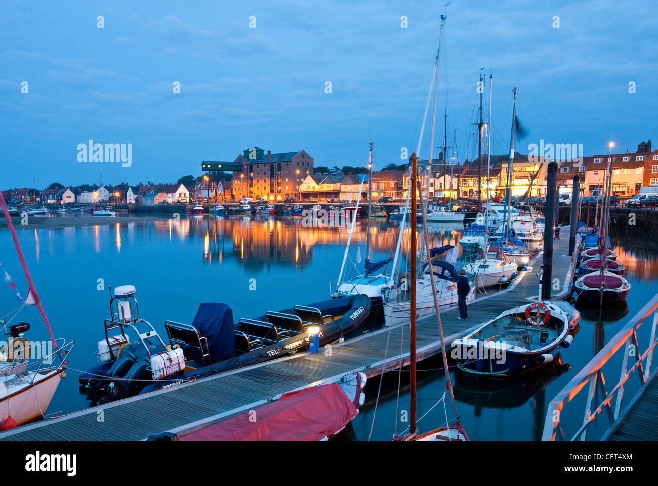 Boats moored alongside a jetty in the quay at Wells-next-the-Sea on the North Norfolk coast at night. - Stock Image