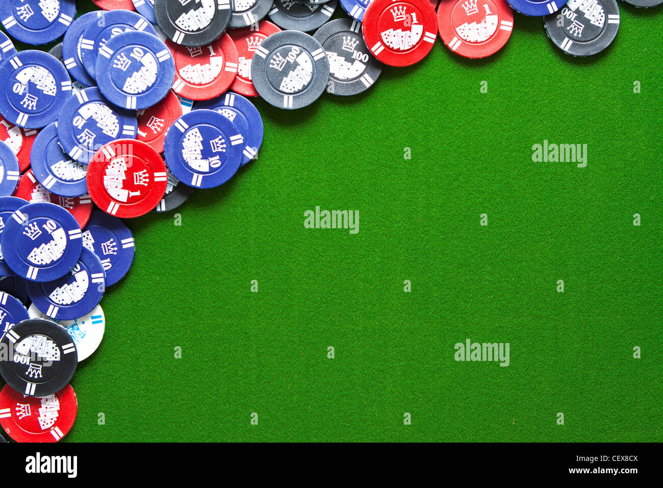 Colorful gambling chips on green felt background with copy space - Stock Image