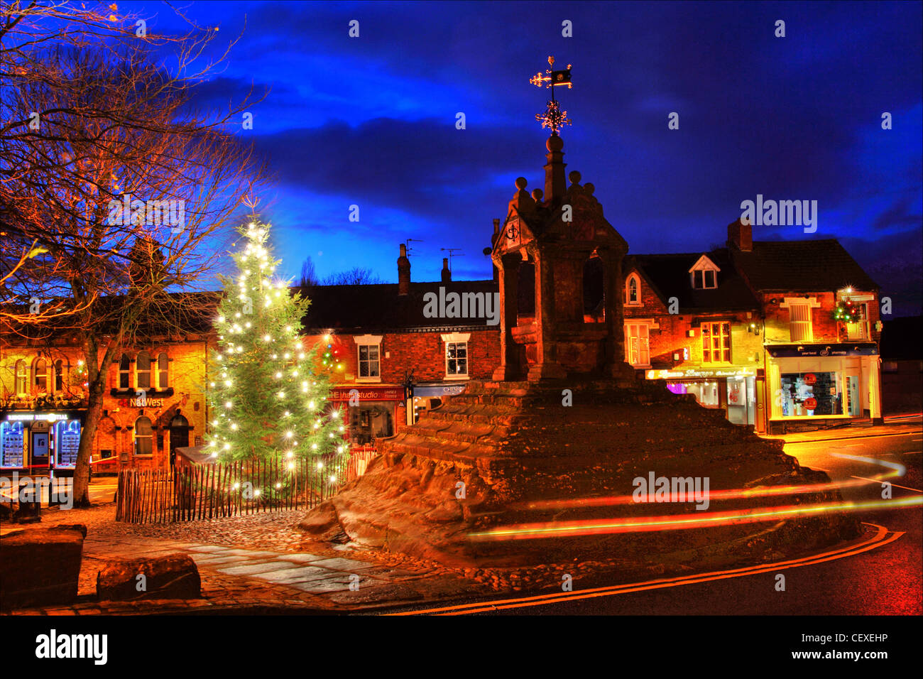 Xmas at the Christmas Tree at Lymm Cross,Lymm village,Cheshire,England,UK,WA13,0HP,WA130HP,winter,snowless,scene,scenes,lights,treelights,treelight,gotonysmith,dusk,night,shot,blue,hour,bluehour,25th,december,cold,frosty,evening,LymmCross,scene,gotonysmith,Buy Pictures of,Buy Images Of,Lymm Cross is in the village of Lymm,Cheshire,England.,It,has,been,designated,by,English,Heritage,as,a,Grade,I,listed,building.,The,cross,dates,from,the,early,to,the,middle,17th,century,and,it,was,restored,in,1897.,It,is,constructed,of,sandstone,and,stands,on,an,artificially,stepped,natural,outcrop,of,red,sandstone.,Its,shaft,stands,in,a,square,pavilion,of,red,sandstone,with,square,corner,pillars.,It,has,a,stone,roof,with,a,pedimented,gable,to,each,face,and,ball,finials.,Above,the,cross,is,an,extension,which,carries,a,stone,ball,and,an,ornate,weather,vane.,On,the,east,south,and,west,gables,are,bronze,sundials,of,1897,carrying,the,inscriptions,and,1,We are a Shadow,Save Time,Think of the Last