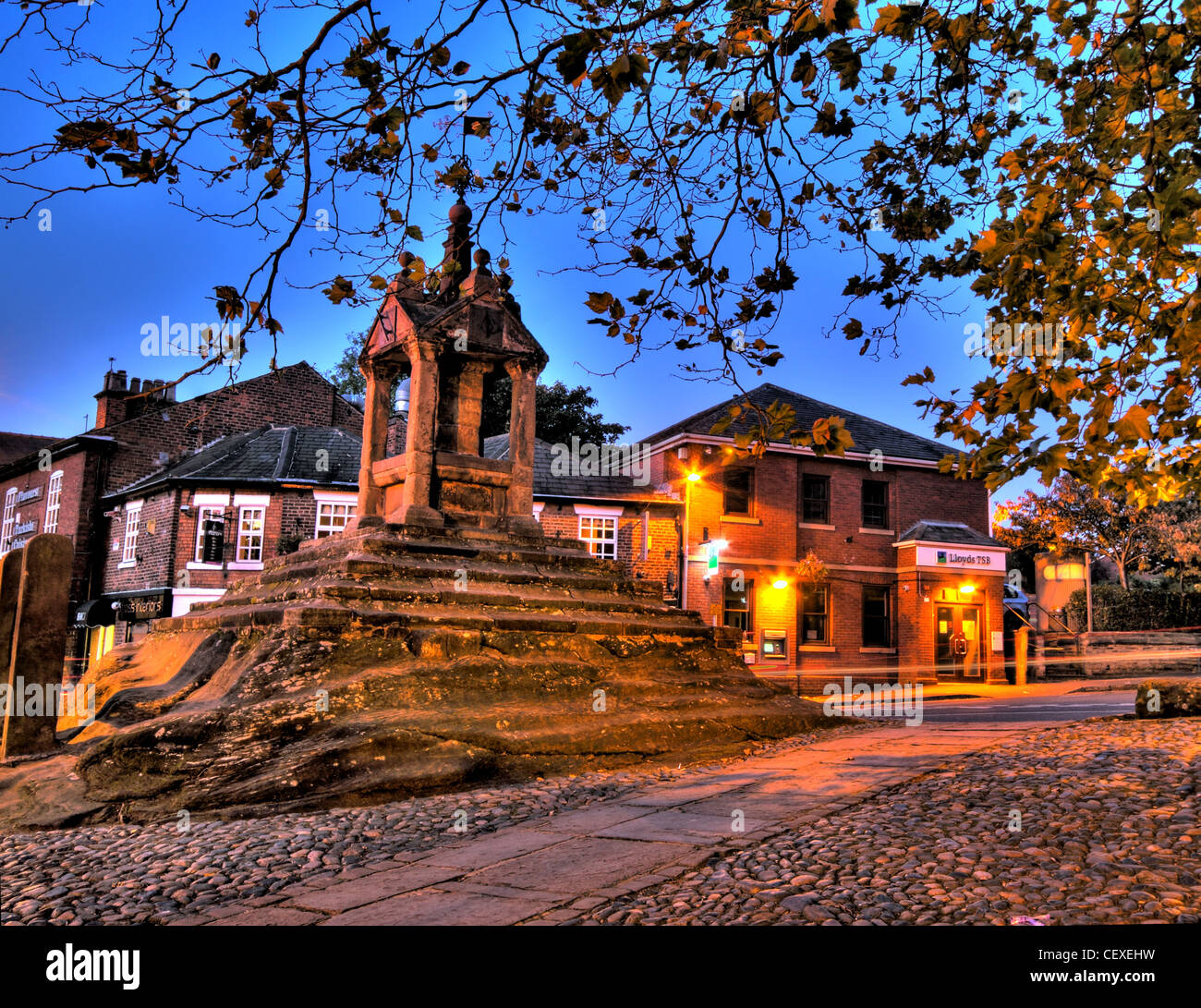Autumn,Fall,at,Lymm,Cross,Lymmvillage,Cheshire,England,UK,WA13,0HP,WA130HP,autumn,cold,scenes,lights,gotonysmith,dusk,night,shot,blue,hour,bluehour,october,evening,LymmCross,scene,picturesque,Lloyds,bank,branch,sub-branch,sub,gotonysmith,Buy Pictures of,Buy Images Of,Lymm Cross is in the village of Lymm,Cheshire,England.,It,has,been,designated,by,English,Heritage,as,a,Grade,I,listed,building.,charming,villages,tourist,tourism,The,cross,dates,from,the,early,to,the,middle,17th,century,and,it,was,restored,in,1897.,It,is,constructed,of,sandstone,and,stands,on,an,artificially,stepped,natural,outcrop,of,red,sandstone.,Its,shaft,stands,in,a,square,pavilion,of,red,sandstone,with,square,corner,pillars.,It,has,a,stone,roof,with,a,pedimented,gable,to,each,face,and,ball,finials.,Above,the,cross,is,an,extension,which,carries,a,stone,ball,and,an,ornate,weather,vane.,On,the,east,south,and,west,gables,are,bronze,sundials,of,1897,carrying,the,inscriptions,and,We are a Shadow,Save Time,Think of the Last