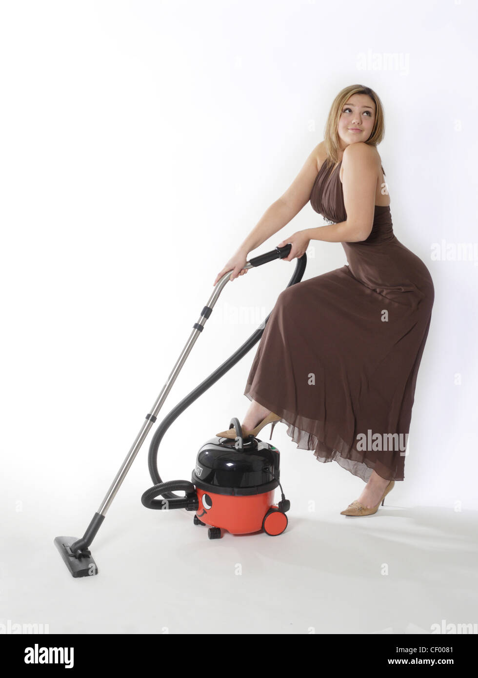 Teenage girl, long dark blonde hair, hazel brown eyes in a brown ball gown gazing wistfully whilst using a vacuum Stock Photo