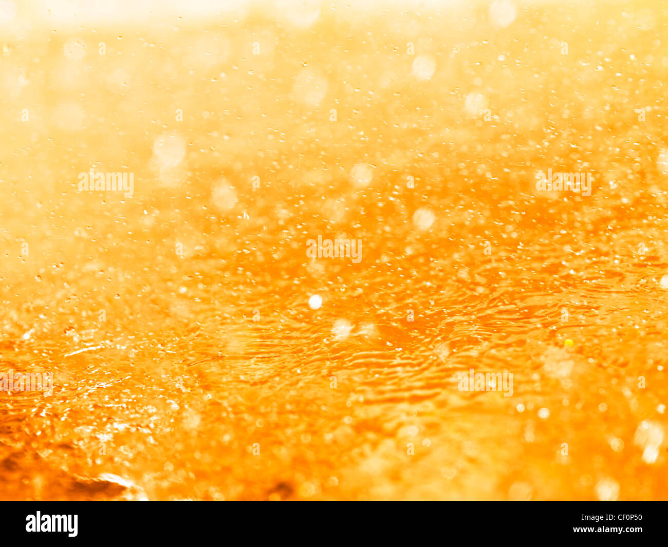Orange splashing liquid closeup abstract background texture - Stock Image
