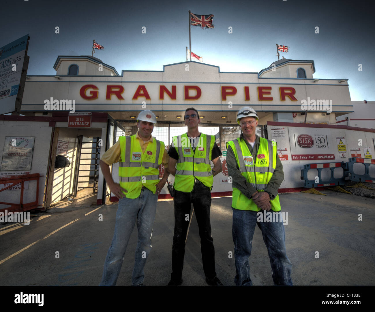 Construction,workers,putting,final,touches,to,the,Grand,Pier,ruined by fire,at,Weston,Super,Mare,Avon,England,UK,gotonysmith,workers,sisk,reopen,reopening,sea,side,seaside,holiday,summer,men,three,union,jack,flag,The,Grand,Pier,is,a,pier,in,Weston-super-Mare,North Somerset,England.,It,is,situated,on,the,Bristol,Channel,approximately,18,miles,(29,km),south,west,of,Bristol.,gotonysmith,The,pier,is,privately-owned,and,is,one,of,three,piers,in,the,town,together,with,Birnbeck,Pier,which,stands,derelict,awaiting,possible,restoration,and,the,much,shorter,SeaQuarium,aquarium,built,towards,the,south,end,of,the,seafront.,It,is,supported,by,600,iron,piles,and,is,400,metres,(1,300,ft),long.,It,has,been,damaged,by,fire,on,two,occasions,in,1930,and,2008.,Following,the,latter,fire,which,completely,destroyed,the,pavilion,the,pier,was,rebuilt,at,a,cost,of,£39,million,and,reopened,on,23,October,2010,Buy Pictures of,Buy Images Of