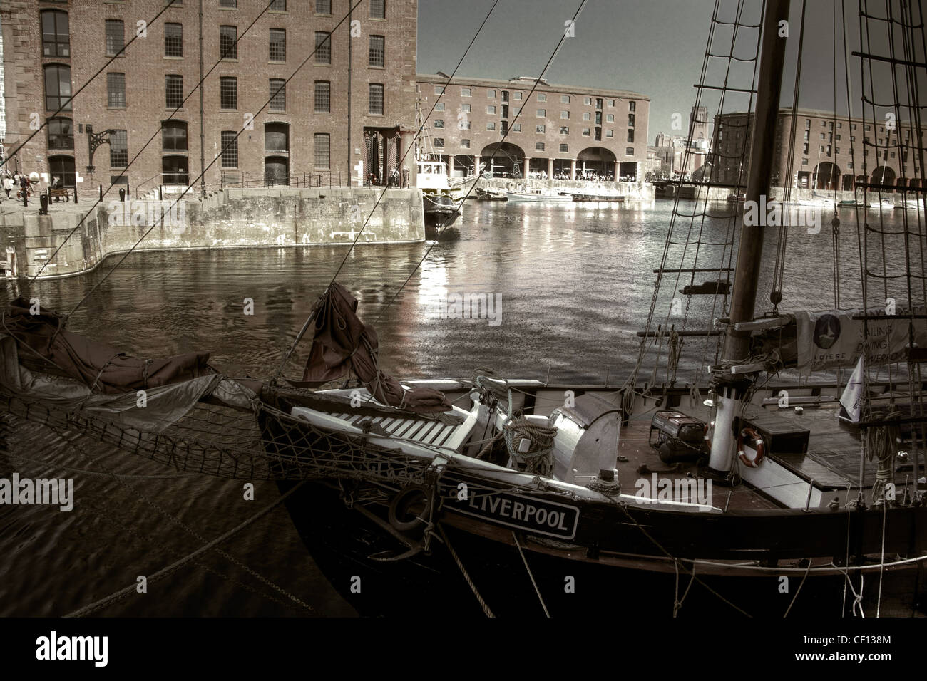 Livrpool,gotonysmith,liverpol,liverpool,mersyside,merseyside,dock,building,rigger,sailship,sail,ship,beatle,city,beatles,beatlesss,northwest,north,west,england,history,historic,boatyard,boat,yard,docks,wet,UNESCO,gotonysmith,Buy Pictures of,Buy Images Of,Albert,Dock,is,a,complex,of,dock,buildings,and,warehouses,in,Liverpool,England. Designed by Jesse Hartley and Philip Hardwick,it was opened in 1846,and,was,the,first,structure,in,Britain,to,be,built,from,cast,iron,brick and stone,with no structural wood. As a result,it was the first non-combustible warehouse system in the world.,At,the,time,of,its,construction,the,Albert,Dock,was,considered,a,revolutionary,docking,system,because,ships,were,loaded,and,unloaded,directly,from/to,the,warehouses.,Two,years,after,it,opened,it,was,modified,to,feature,the,worlds,first,hydraulic,cranes.,Due,to,its,open,yet,secure,design,the,Albert,Dock,became,a,popular,store,for,valuable,cargoes,such,as,brandy,cotton,tea,silk,tobacco,ivory and sugar. However,despite the Albert Docks advanced design,the rapid development of shipping technology,1