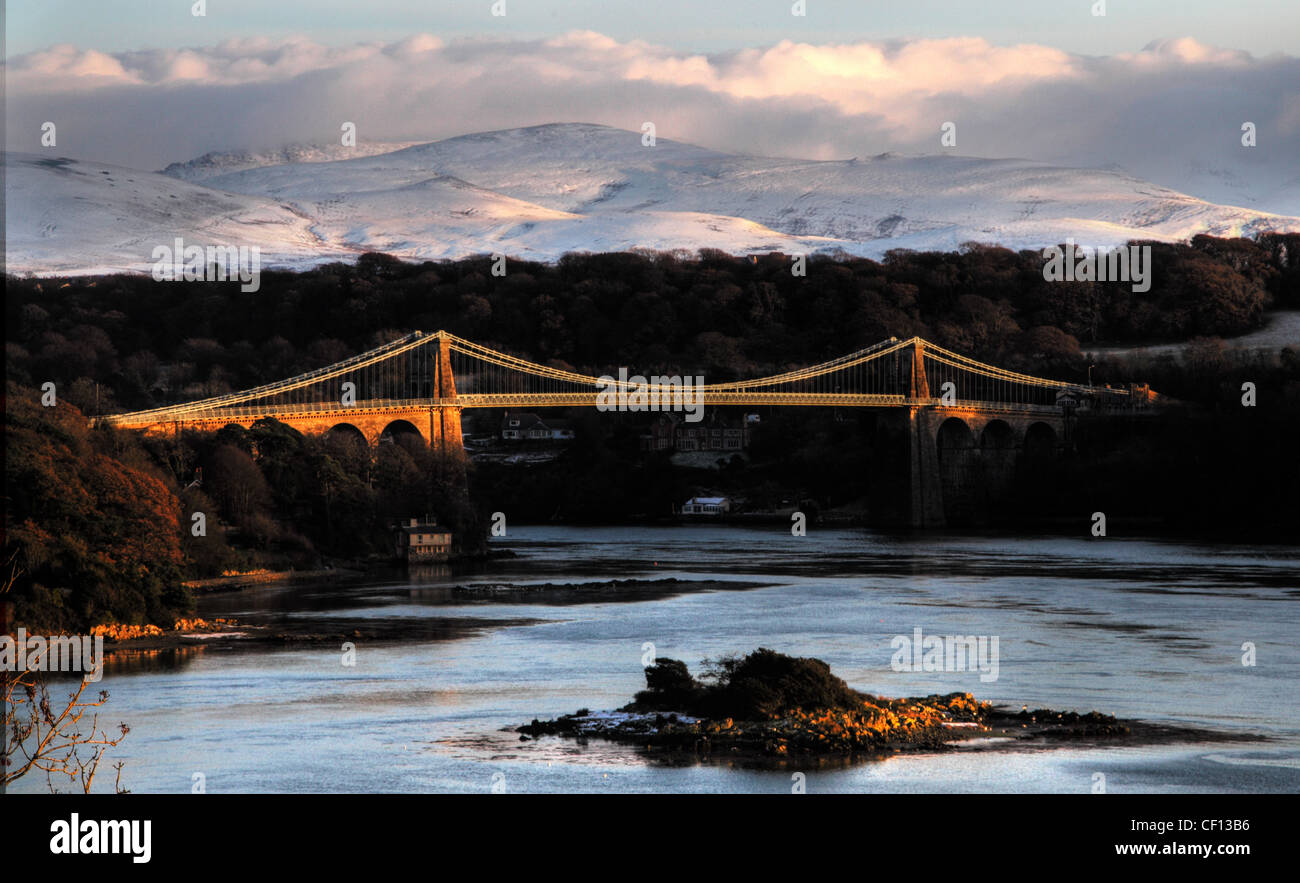 Angelsey Menai Bridge in Snow,winter,water,low,sun,sunset,sunrise,orange,blue,wales,cymu,Cymru,north,wales,ynys,mon,straits,strait,Anglesey,is,also,the,largest,island,in,the,Irish,Sea.,Wales,is,largely,mountainous,gotonysmith highest peaks in the north and central areas,Snowdonia Snowdon,tides,tidal,small,country,countries,icon,iconic,celtic,Menai,Suspension,Bridge,shown,here,carrying,the,A5,in,winter,gotonysmith,Buy Pictures of,Buy Images Of
