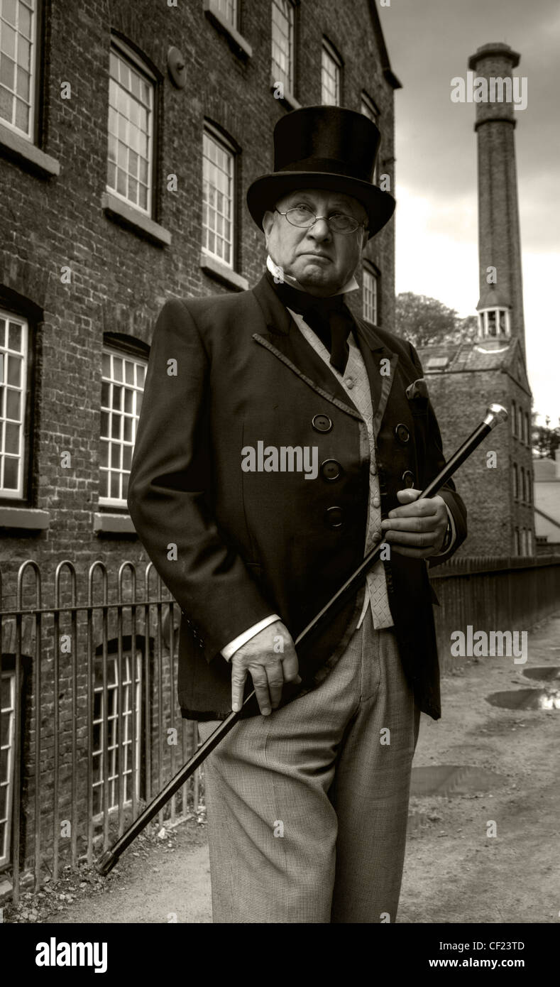 The Victorian industrial mill Owner,Styal,close to Manchester,Cheshire,England,United,Kingdom,gotonysmith,portrait,actor,sepia,black,white,b/w,mono,monochrome,chimney,satanic,gothic,glasses,hat,cane,stick,in,hand,suit,jacket,cravat,NT,national,trust,Quarry Bank Mill in Cheshire,England,is,one,of,the,best,preserved,textile,mills,of,the,Industrial,Revolution,and,is,now,a,museum,of,the,cotton,industry.,It,is,a,Grade,II,listed,building,and,is,now,in,the,care,of,the,National,Trust.,The,mill,was,founded,by,Samuel,Greg,(who,is,represented,here),in,1784,in,the,village,of,Styal,on,the,River,Bollin.,Its,original,iron,water,wheel,was,designed,by,Thomas,Hewes,and,built,between,1816,and,1820.,The,Hewes,wheel,finally,broke,in,1904.,After,that,the,River,Bollin,continued,to,power,the,mill,through,two,water,turbines.,Today,the,Mill,is,home,to,the,most,powerful,working,waterwheel,in,Europe,an,iron,water,wheel,which,was,originally,at,Glasshouses,Mill,at,Patley,Bridge.,This,wheel,was,designed,by,Sir,William,Fairbairn,the,Scottish,engineer,who,had,been,an,apprentice,of,Thomas,Hewes.,The,estate,surrou
