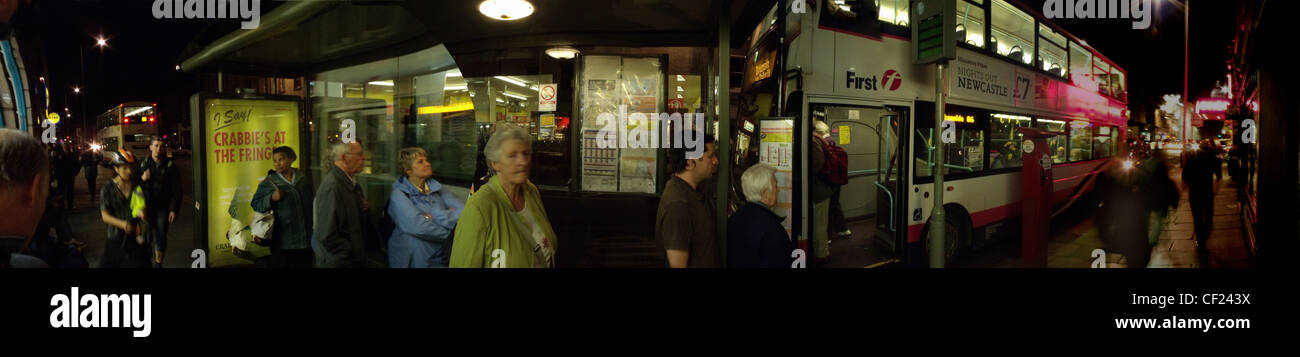 A First bus at a bus shelter,North,Bridge,St,Edinburgh,Evening,shot,taken,as,panorama.,City,public,transport.,people,queue,street,gotonysmith,waiting,traffic,publictransport,nightbus,Scotland,Scottish,timetable,timetables,pano,panorama,buses,Lothian,buses,First,omnibus,route,routes,south,north,nighttime,early,evening,late,heading,home,best,really,good,gotonysmith,Buy Pictures of,Buy Images Of