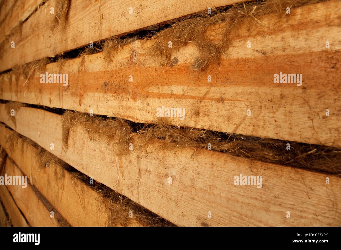 Wall of barn of rough planks with oakum receding into distance. Horizontal format. - Stock Image