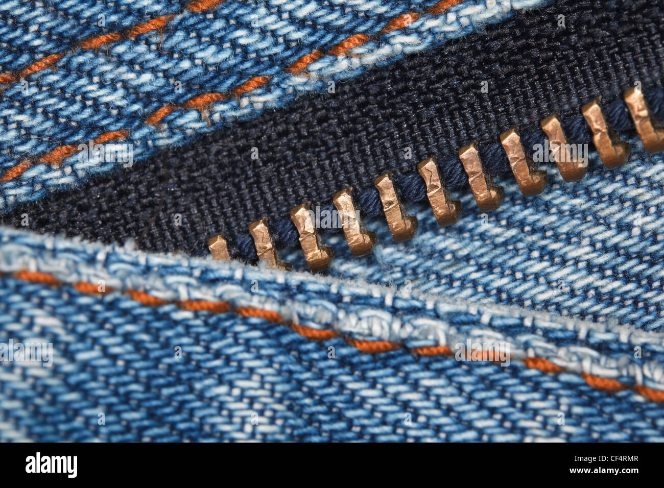 wear a piece of blue denim structure of the yellow line and zipper, macro Stock Photo
