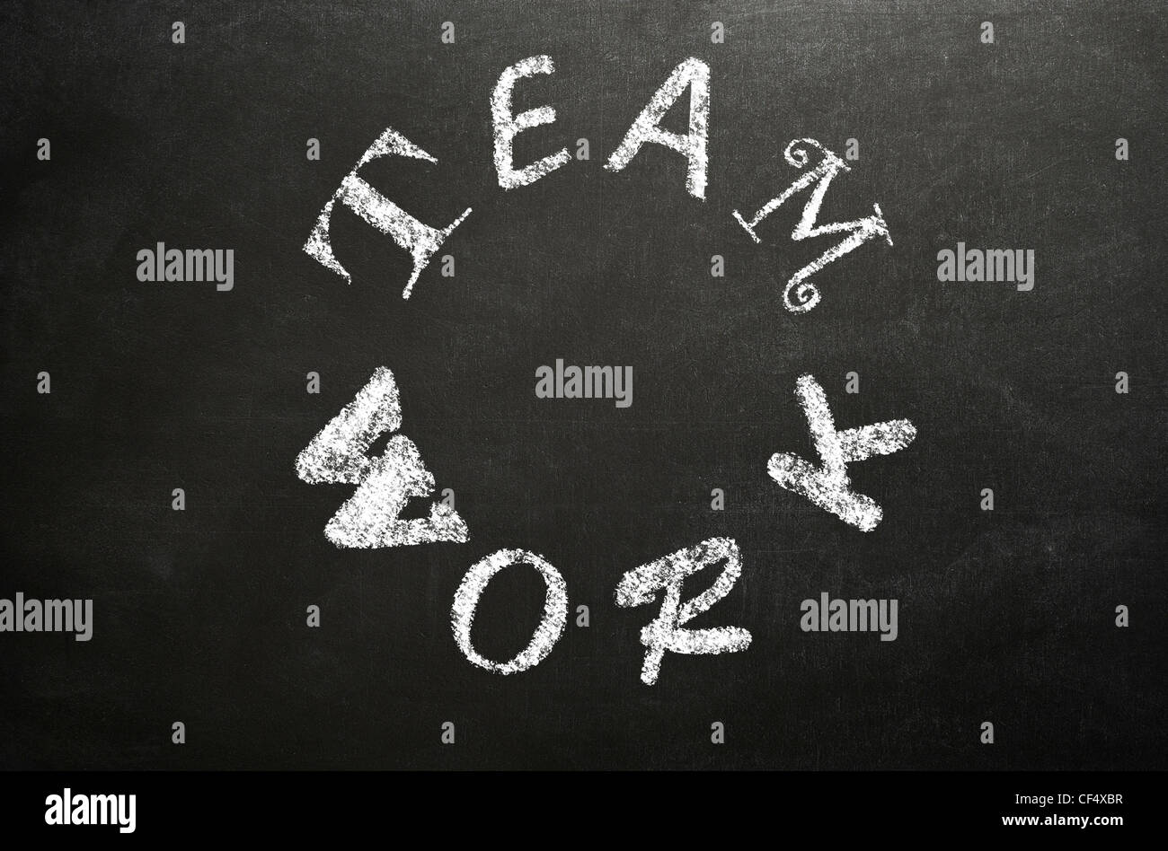 The word 'TEAMWORK' written in a circle in different fonts on a blackboard in white chalk - Stock Image