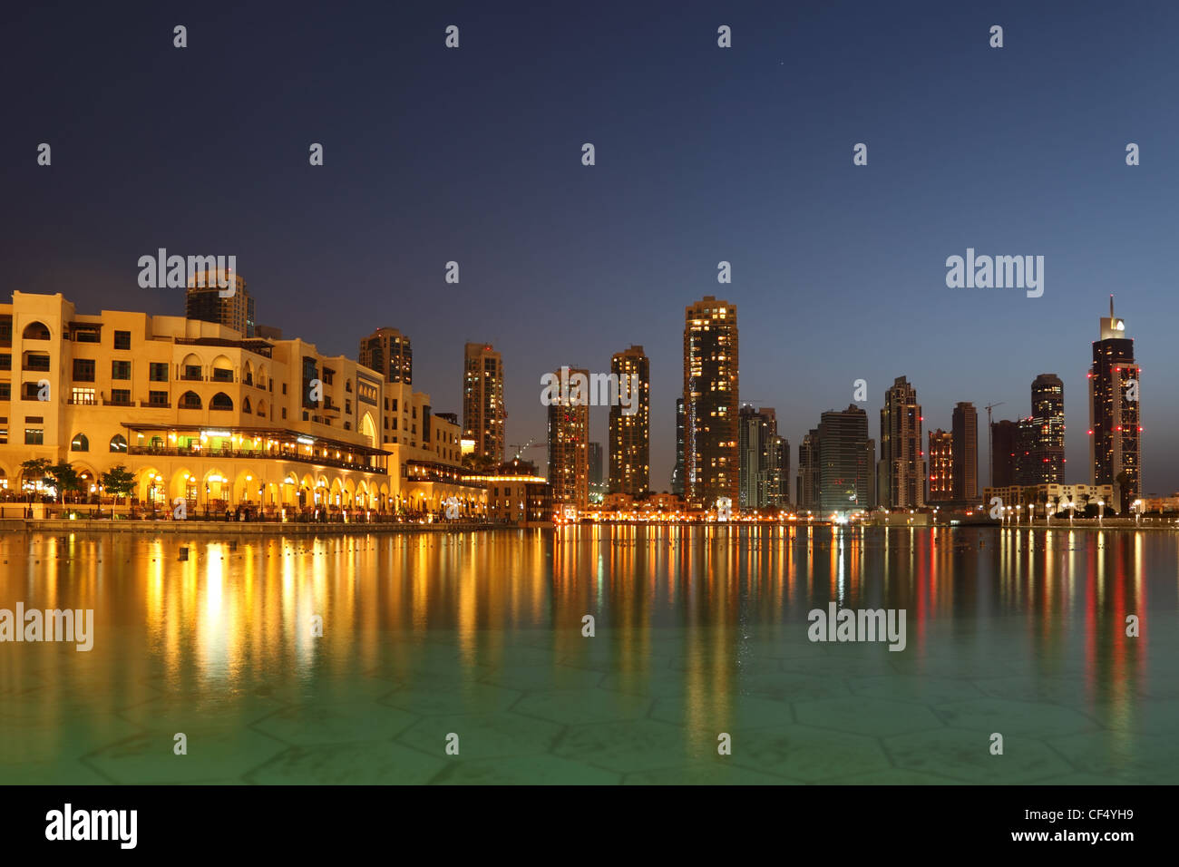 Dubai skyscrapers and other buildings at night time, view from water - Stock Image