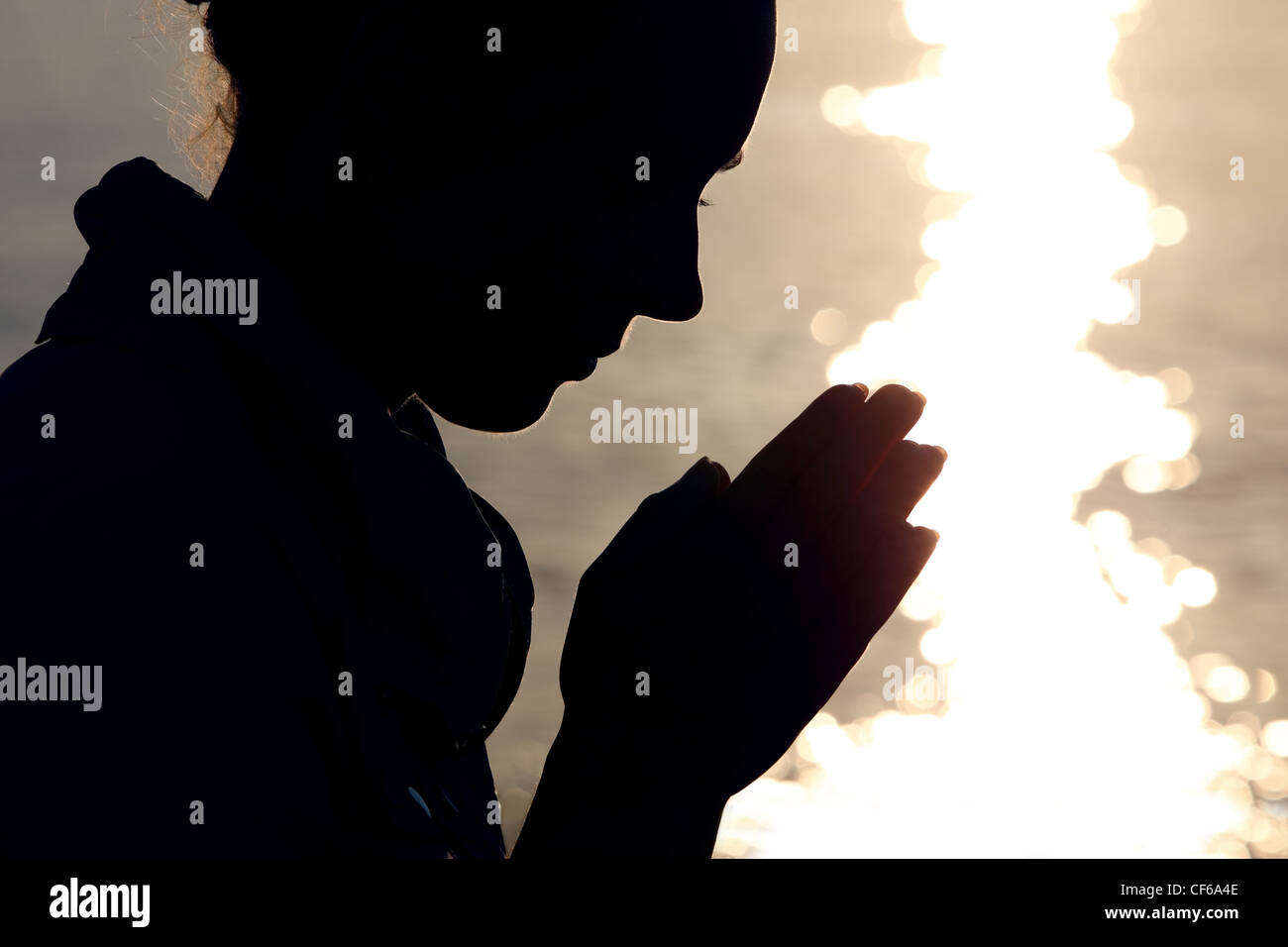 Silhouette of woman in  type, which sits ashore  and prays fold arms - Stock Image