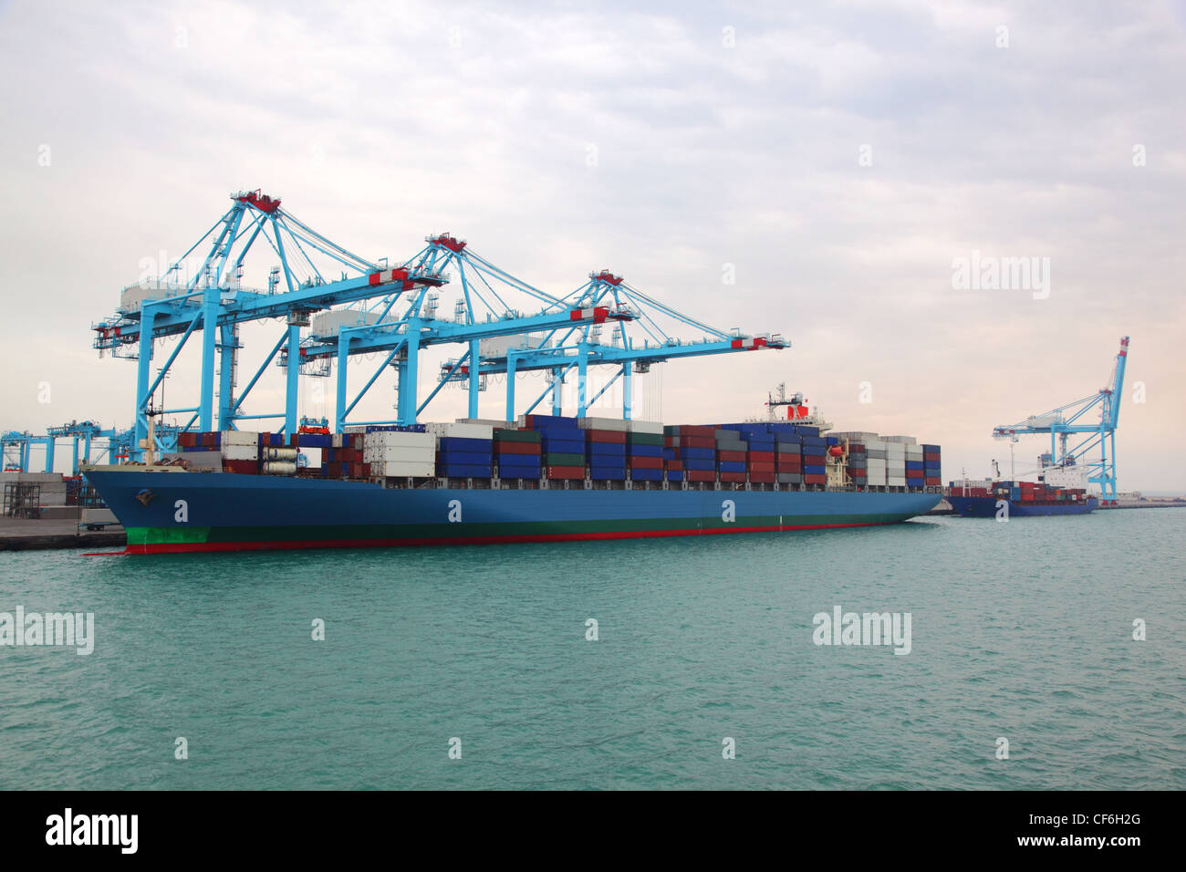 Big cargo boat and small barge docked to industrial port with blue cranes - Stock Image