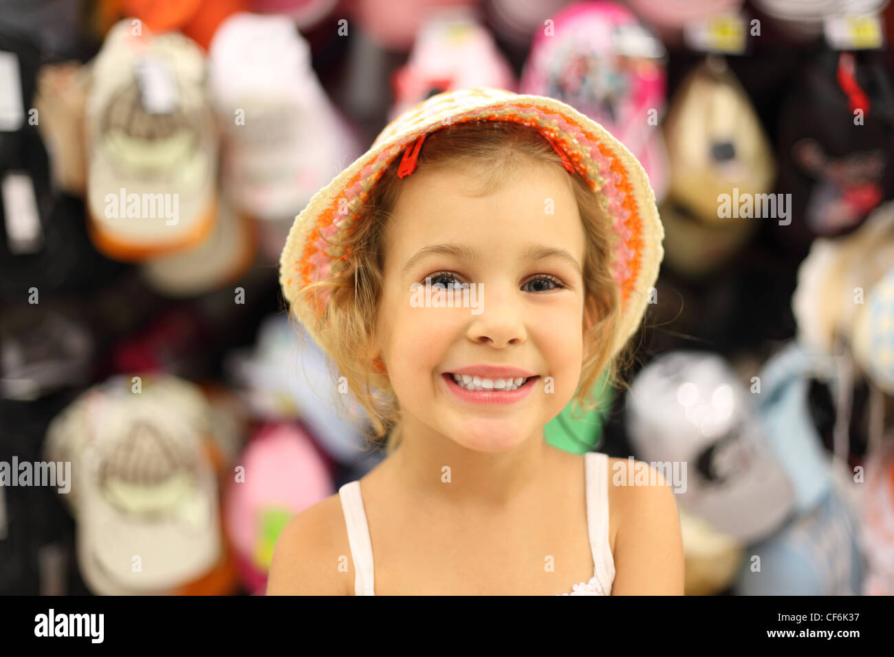 portrait of little girl trying panama in store and smiling, counter with commodity - Stock Image