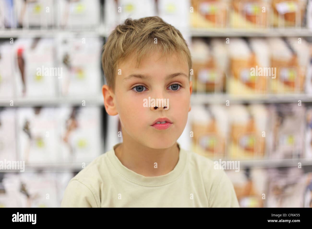 portrait of little caucasian boy looking at side, counter in store with commodity - Stock Image